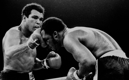 FILE - In this Oct. 1, 1975, file photo, Muhammad Ali's throws a right at Joe Frazier in the 13th round in their title bout in Manila, Philippines. It was, Muhammad Ali would later say, the closest thing to death he had ever known.  He and Joe Frazier had gone 14 brutal rounds in stifling heat off a Philippines morning before Frazier's trainer Eddie Futch mercifully signaled things to an end, his fighter blind and battered and feeling pretty close to death himself. It was 40 years ago and the ``Thrilla in Manilla'' still lives in sporting lore. (AP Photo/FILE)